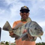 a picture of Capt. Nate holding a black drum he caught in Bradenton