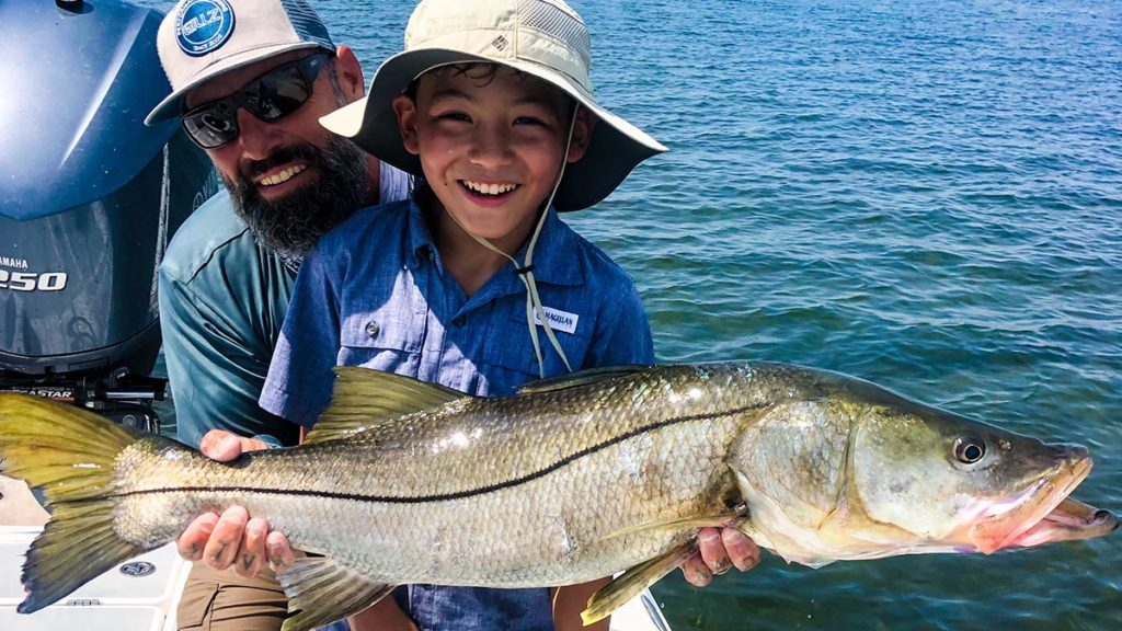 a sarasota fishing guide helping a child hold a fish they caught