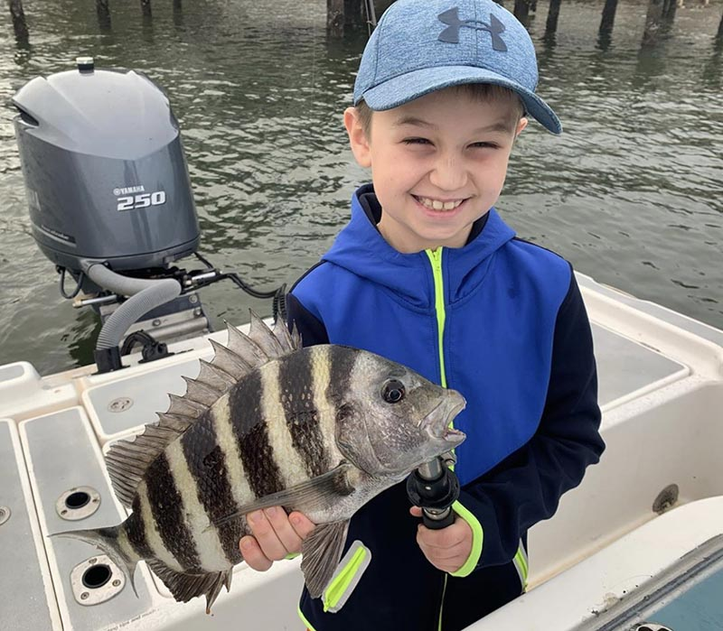 a picture of a young boy holding a sheepshead he caught while on a family friendly fishing charter with Capt. Nate.