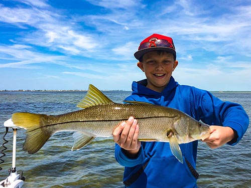 a picture of a child holding a snook he caught while on a family friendly fishing trip with Capt. Nate