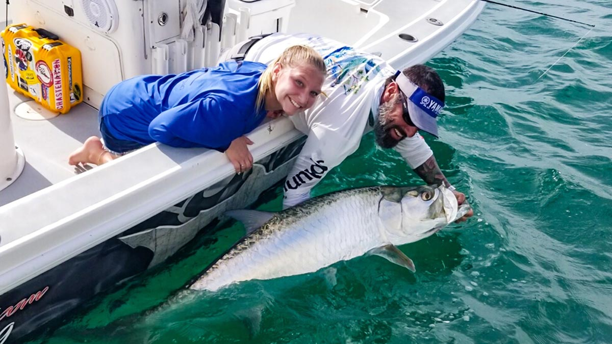 a sarasota fishing guide and client holding a caught tarpon