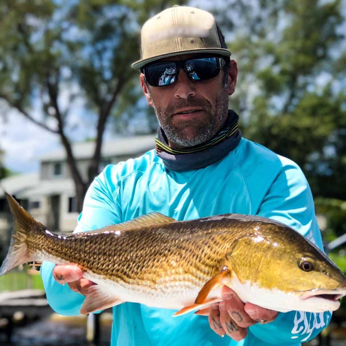 a picture of a fisherman holding a redfish
