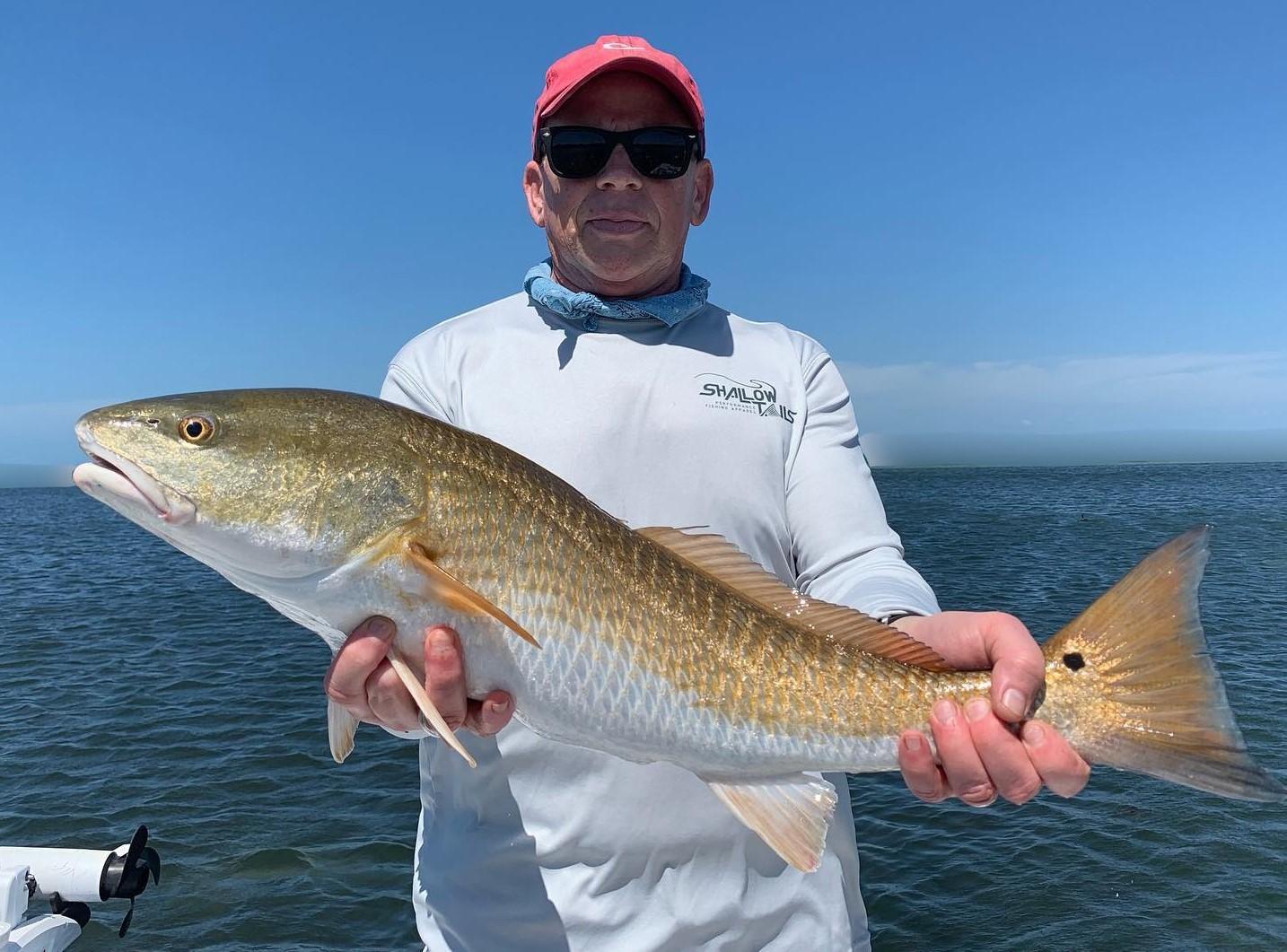 a fisherman who caught a large redfish on a springtime Bradenton fishing charter